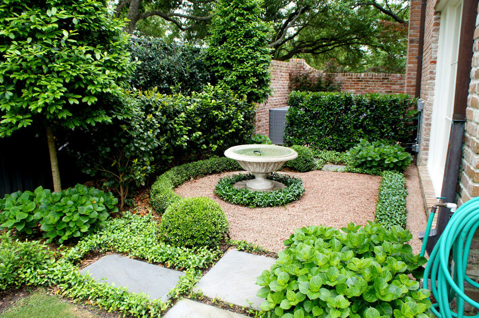 Slate stepping pads lead to a side yard centered around a concrete water feature.