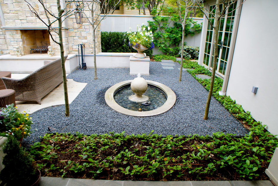 View of finial fountain to show exact lines with pedestal planter of seasonal color. Blackstar gravel and and Sandy Leaf Fig Ivy frame the space.