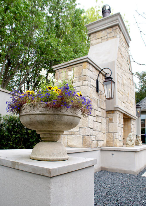 Left:  Season color in a concrete planter rests atop pedestals on either side of the outdoor fireplace.