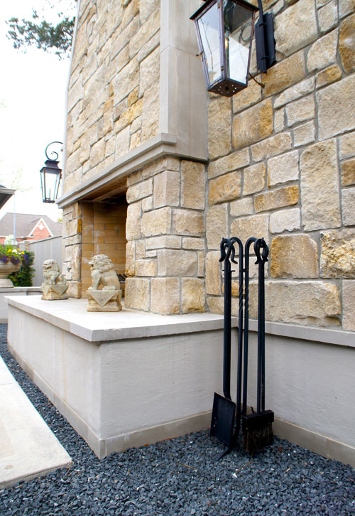 Left:  Side view of outdoor fireplace. Lion statuary and lanterns add to the symmetrical impact of this french-inspired courtyard.