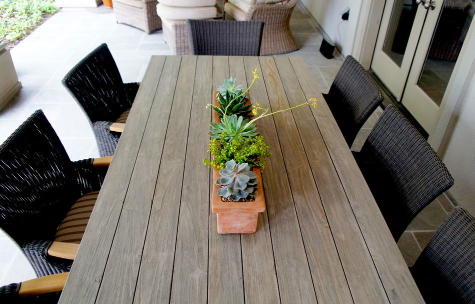 Succulents in a linear terra cotta planter rest atop the outdoor dining table near the courtyard.
