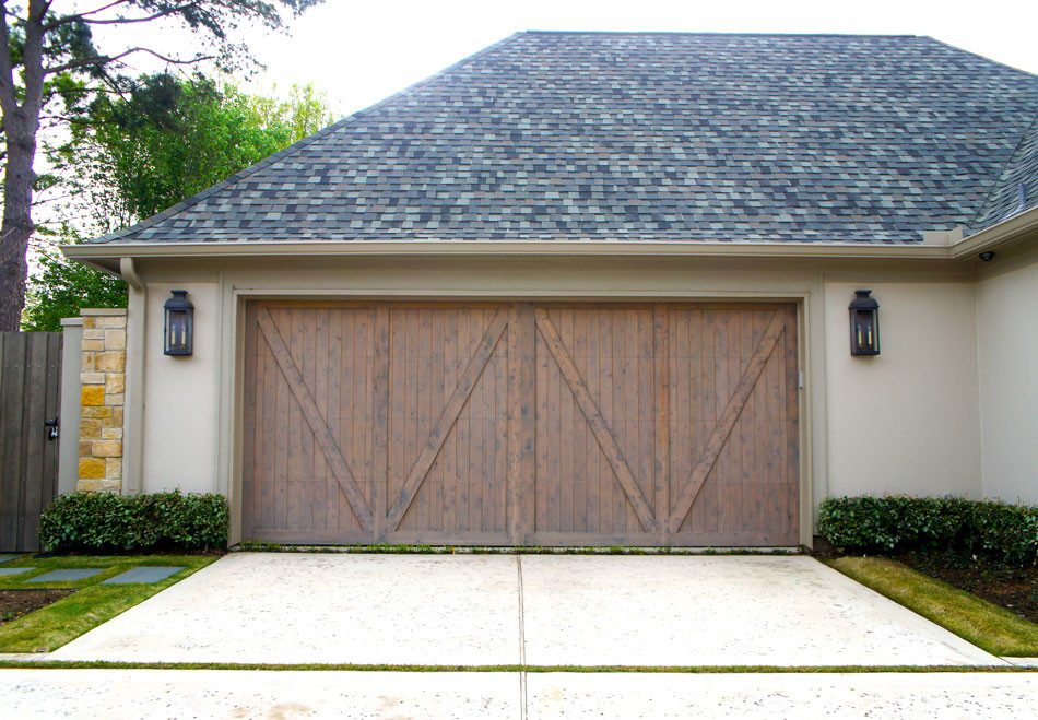 View of garage door. Stone stepping pads lead to gate and driveway was completed with a rock salt finish to add visual interest.