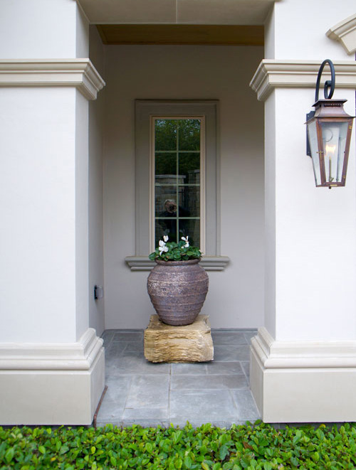 Right:  Cyclamen in a centered planter atop a stone pedestal. Sandy Leaf Fig Ivy line the stone patio.