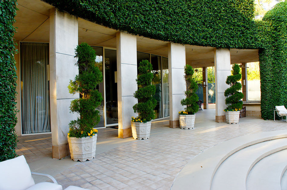 Container grown Italian cypress and spiral juniper add interesting visual elements and a grand, ivy-covered wall give the space a geometric, art deco appeal.