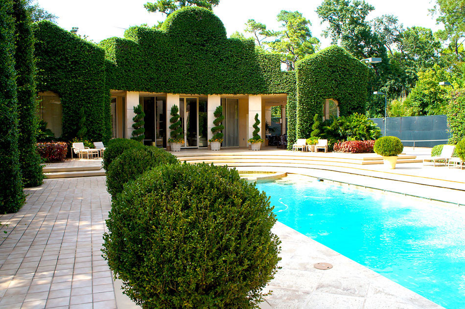 The backyard boasts an ornate, poolside retreat. Container grown Italian cypress and spiral juniper add interesting visual elements and a grand, ivy-covered wall give the space a geometric, art deco appeal. Ivy arches, carved columns, and sharply pruned boxwood spheres create a stunning, yet cohesive, impact.