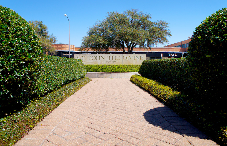 Red brick path leading to sign and lined with pruned boxwood hedges and asian jasmine.