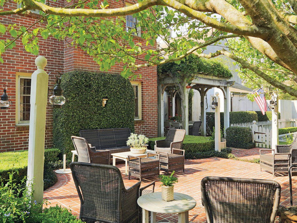 Red brick patio with woven outdoor seating. Ivy covered walls and wisteria covered pergola that frames outdoor dining area. Lamp posts with lanterns and white picket fence add extra detail to this New England style home in Houston, TX.