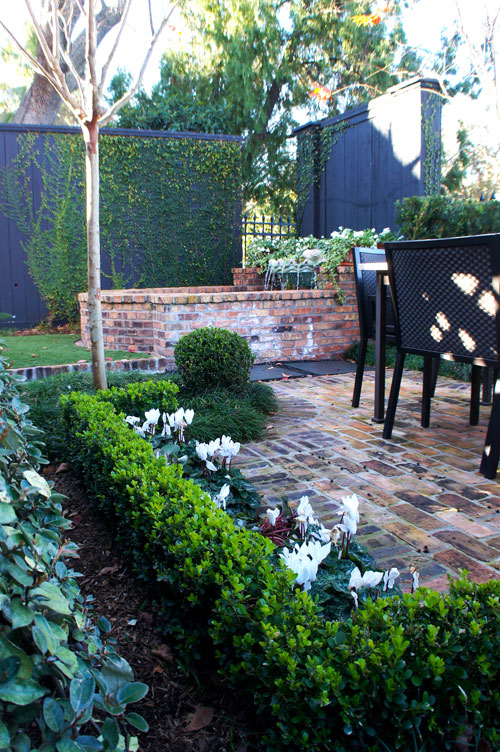 Left:  Brick border separates synthetic lawn from Asian Jasmine and blackstar gravel feature.