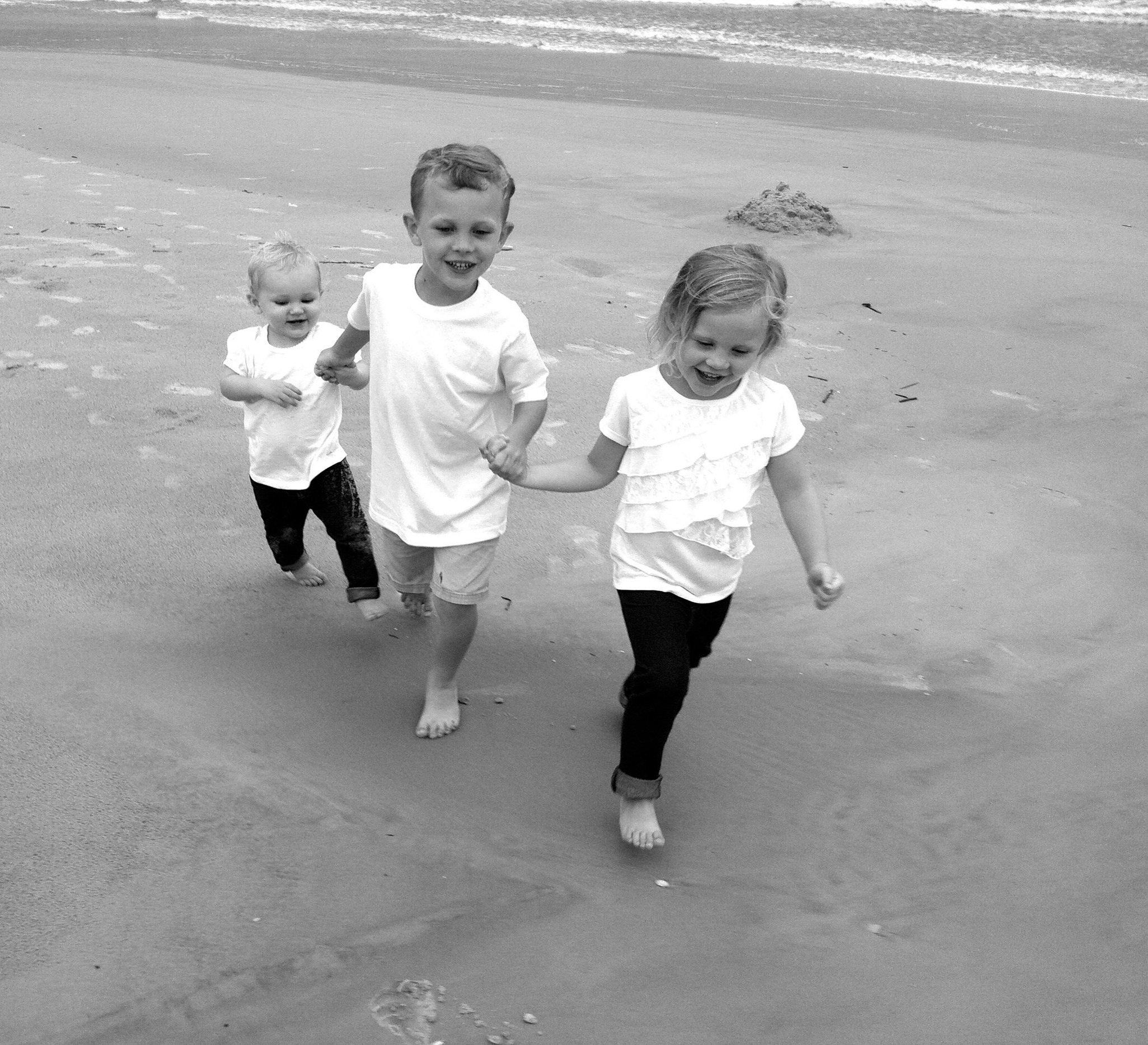 That's our children, Charlotte, Nate, and Ella, walking on St. Augustine Beach in the pre-school years.