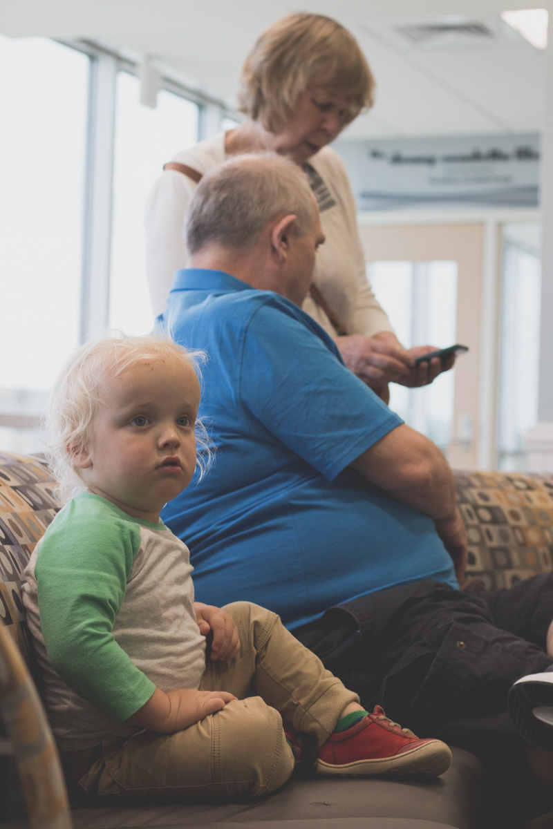 Boy sitting with middle-age seniors in waiting room.
