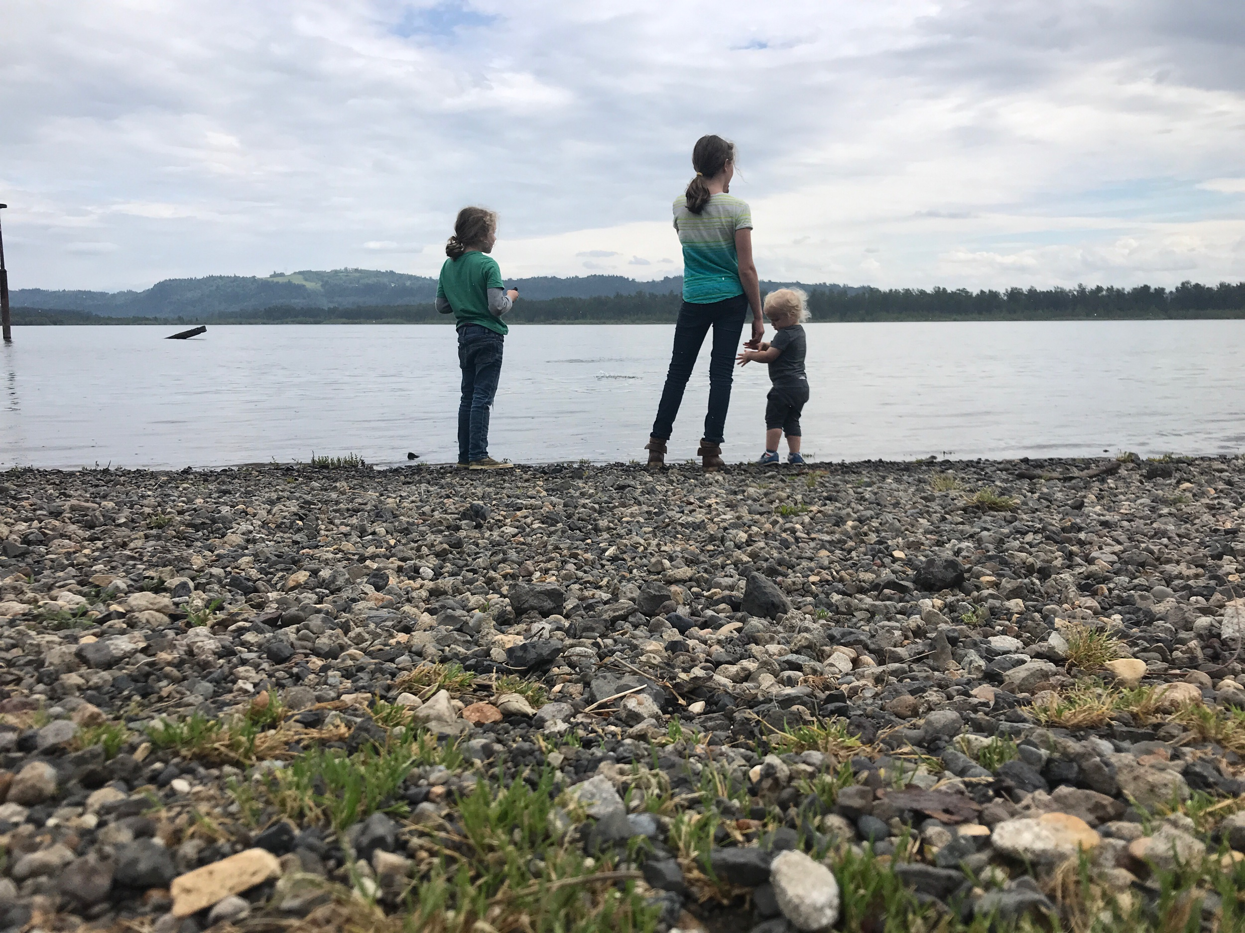Children standing the edge of the Columbia River throwing rocks