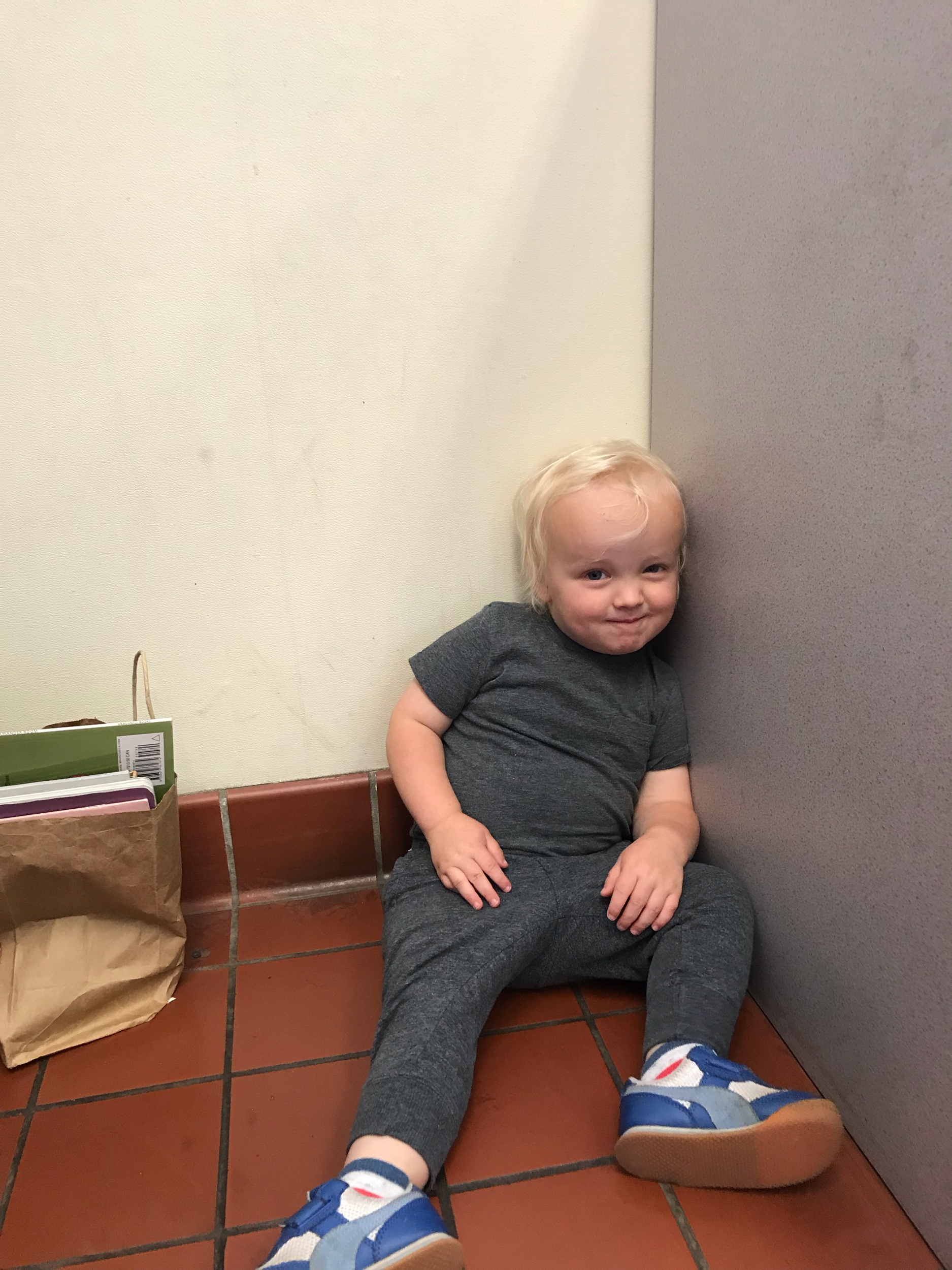 Toddler-age boy sitting in corner of post office with a bag of books.