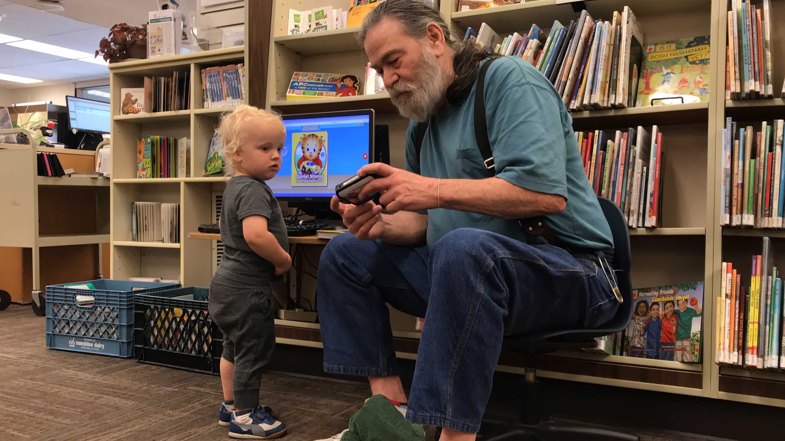 A Washougal Community Library worker with a burly beard assists a toddler-age male patron in the children's section.