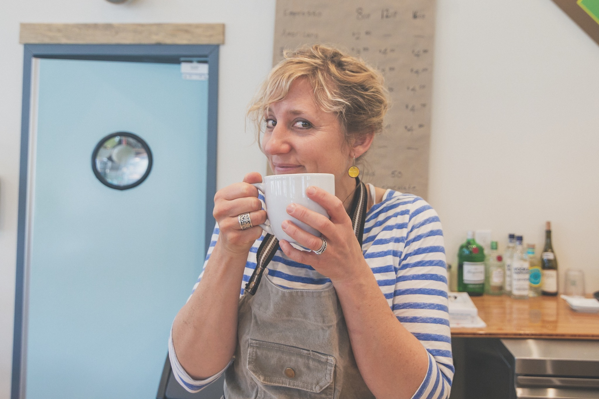 Rachel Nutter, co-owner of The Blythe Cricket, smiles her sparkly smile while holding a mug of Nossa Familia coffee.