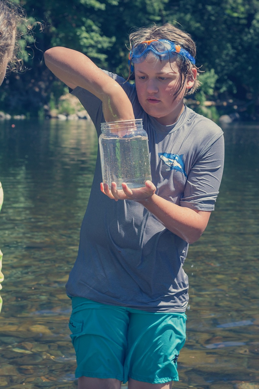 Handsome lad catching a crawdad on a hot summer day on the river.