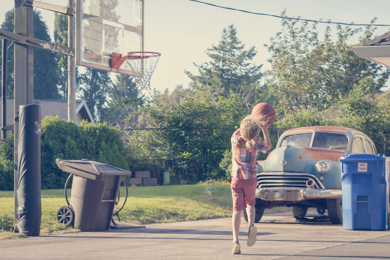 Boy playing basketball by himself with vintage Oldsmobile in background.