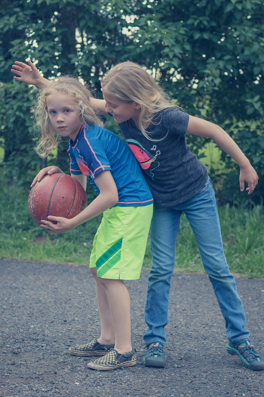 Two elementary-age children playing basketball
