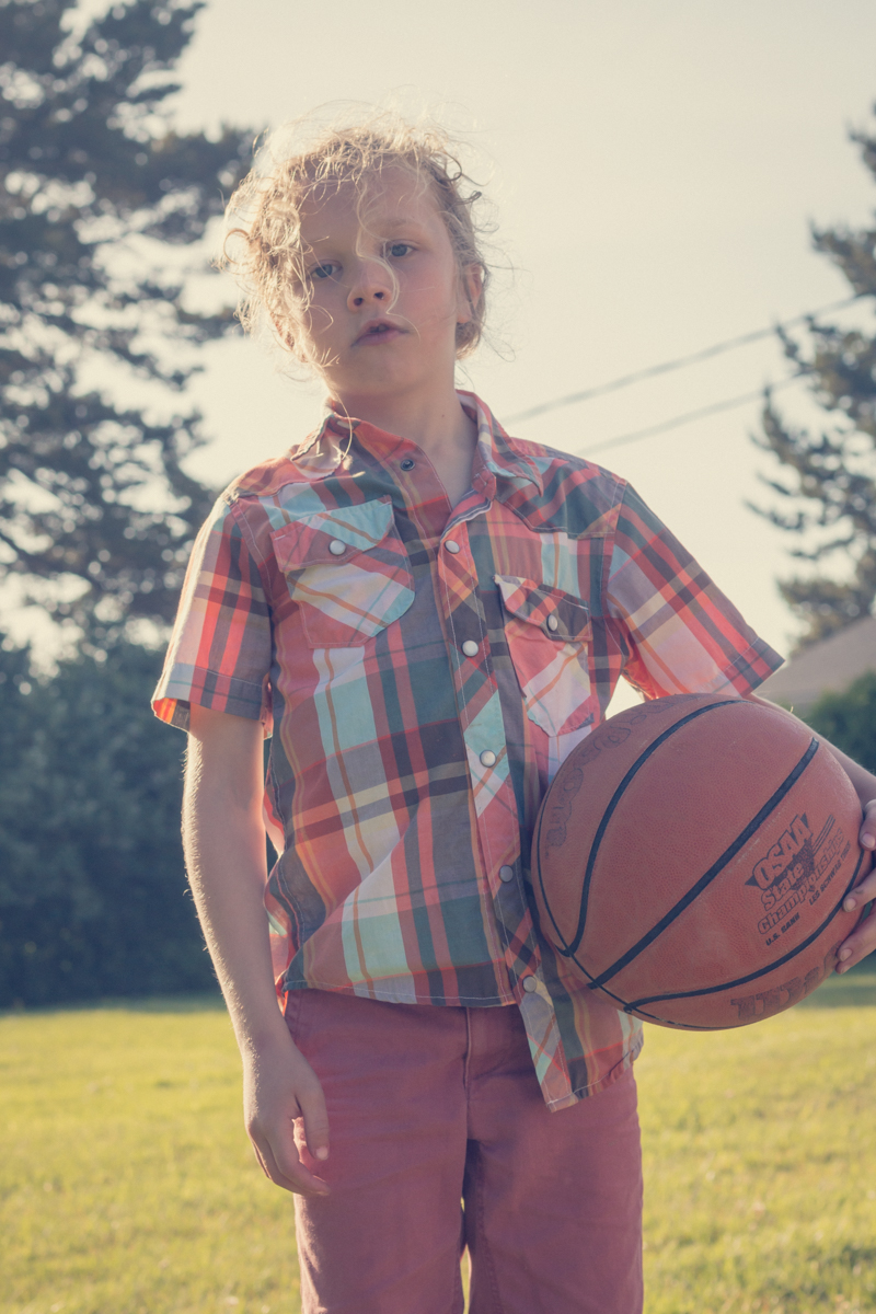 Boy holding basketball on outdoor court