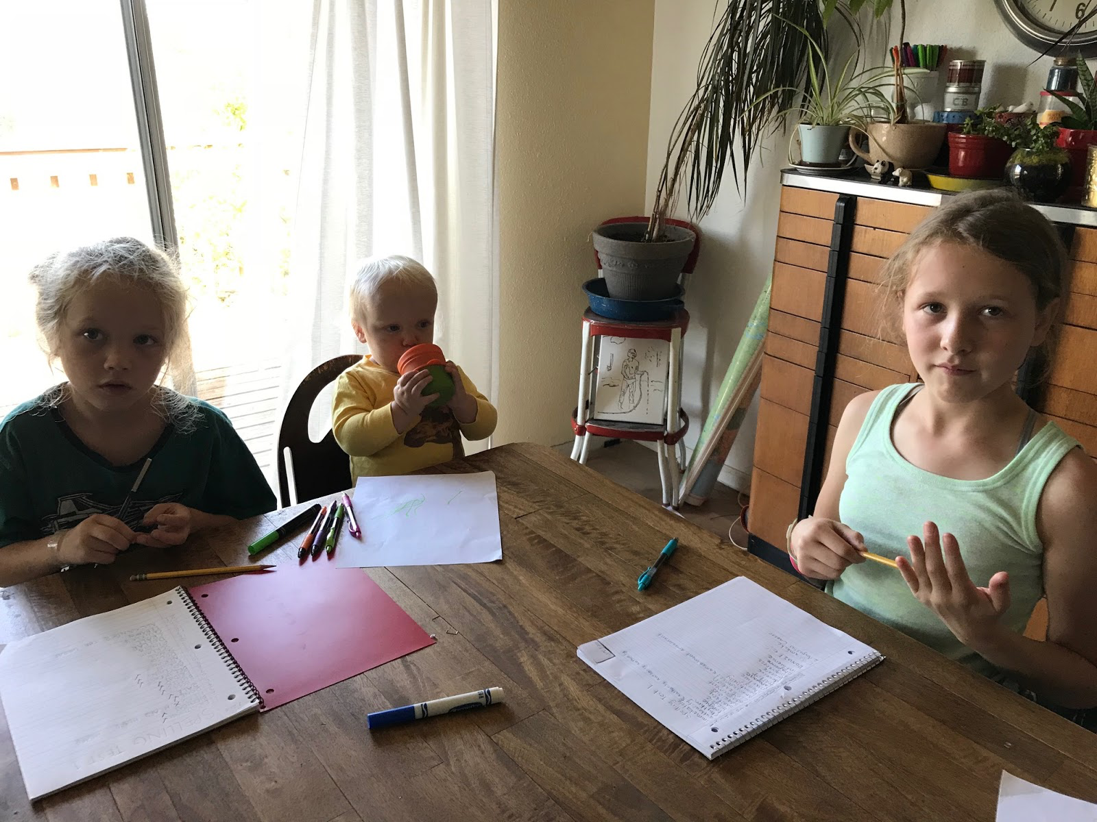 Homeschool children from age 2 to age 11 doing spelling test at table.jpg