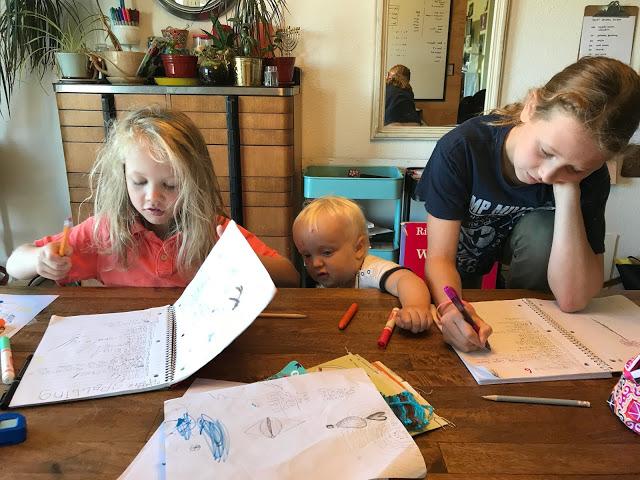three children homeschooling at table