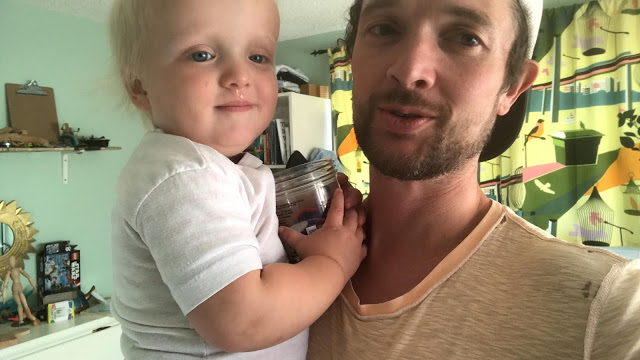 Dad holding two-year old in bedroom before nap