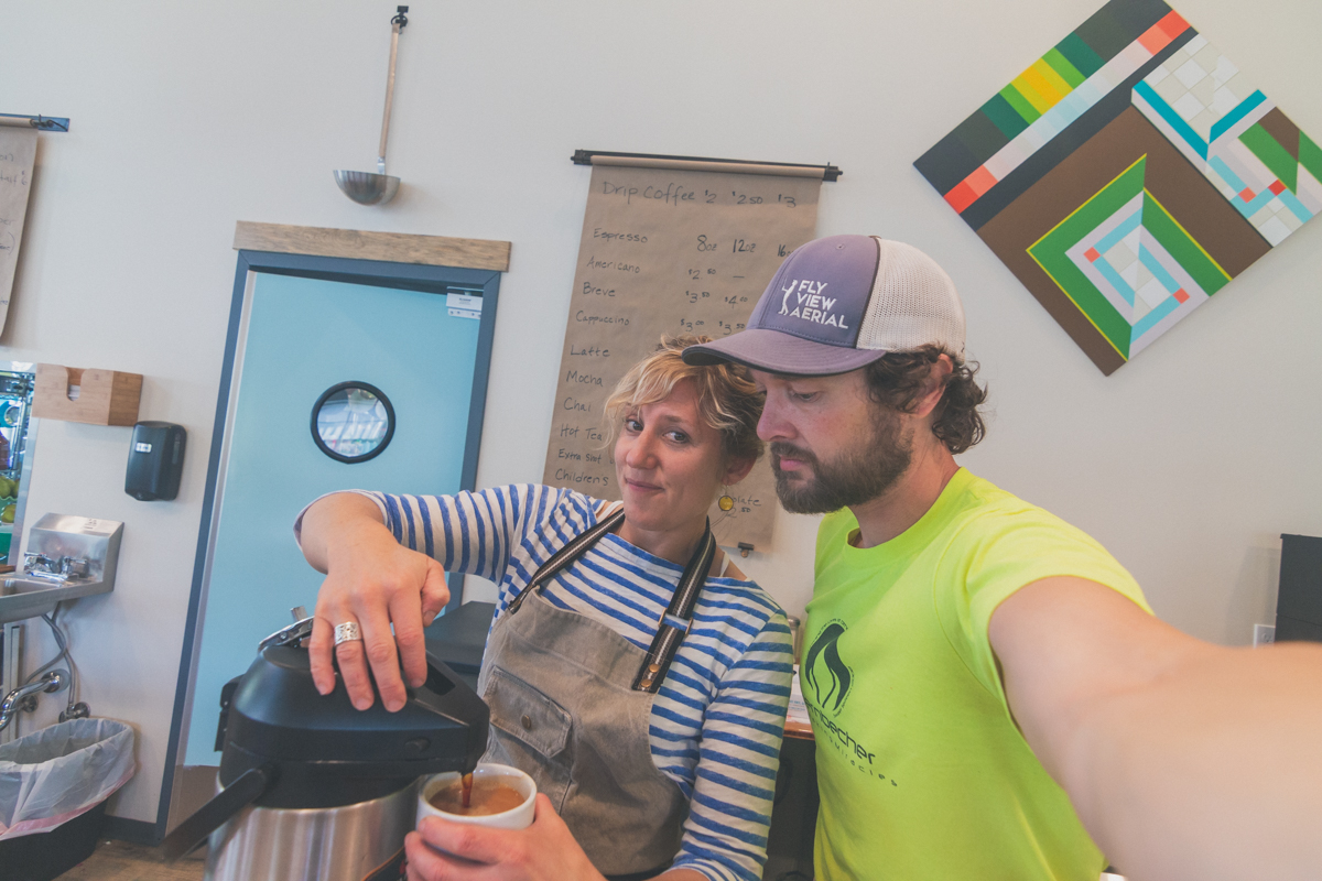 Beautiful woman pouring coffee for bearded fellow taking a selfie