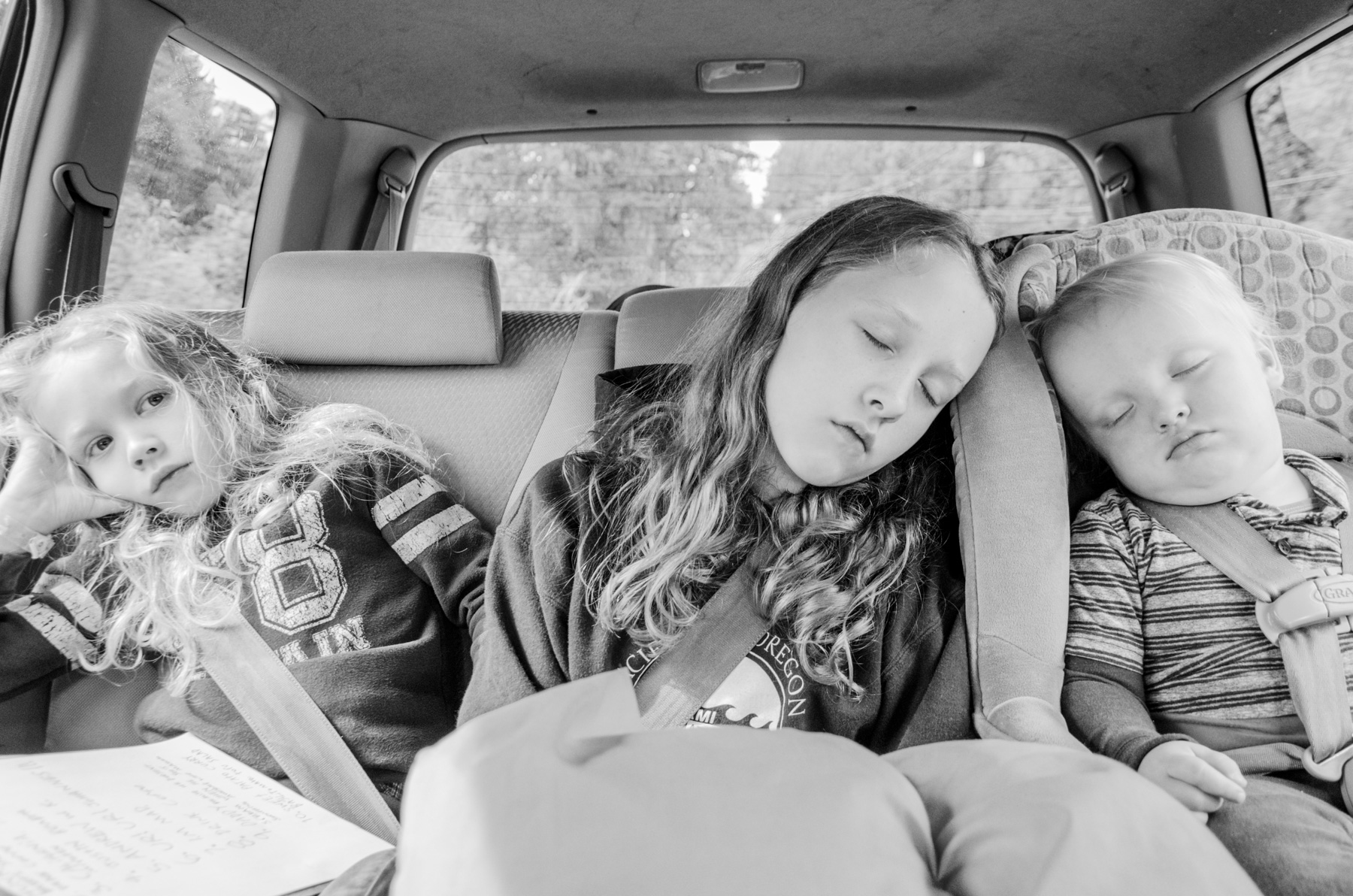 Three children riding in back seat after hiking adventure.