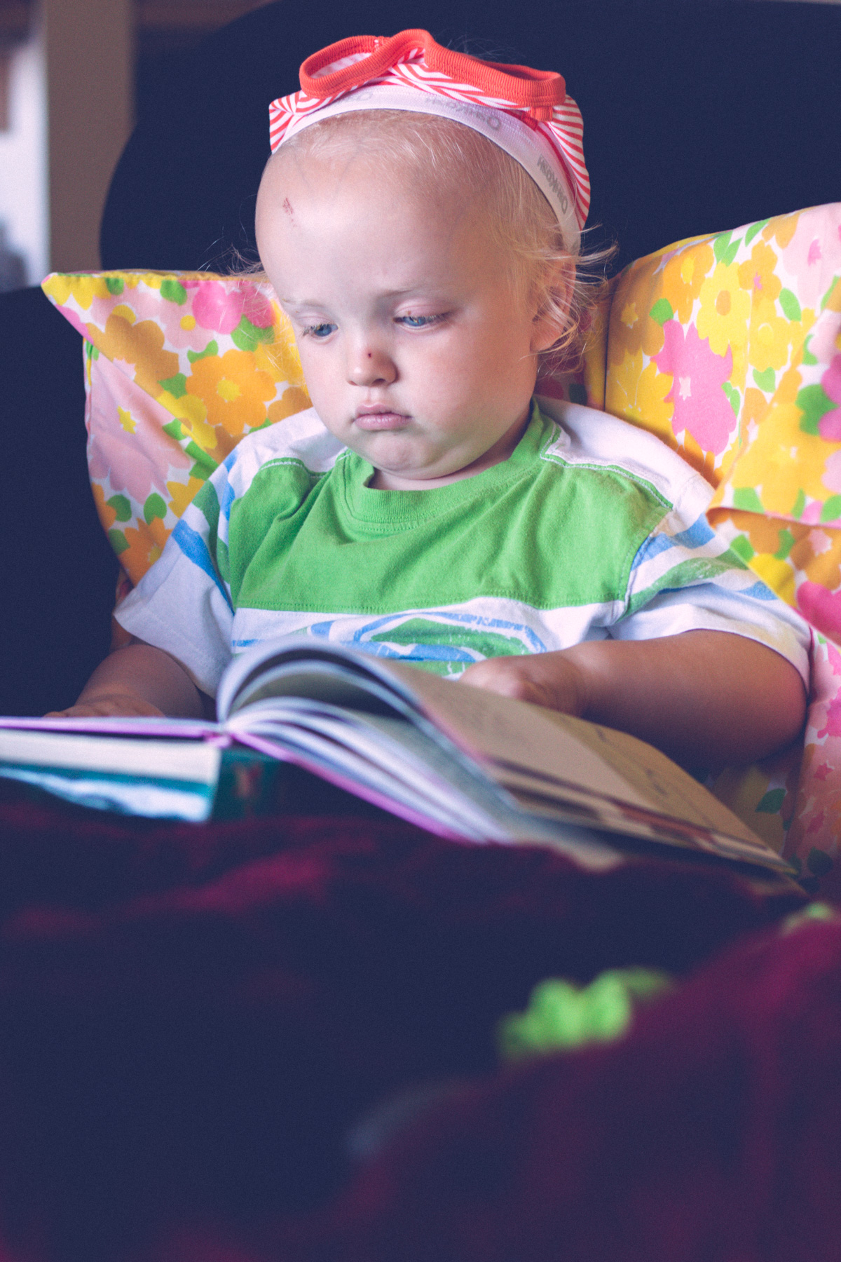 Blond boy reading book on couch while wearing underwear on his head