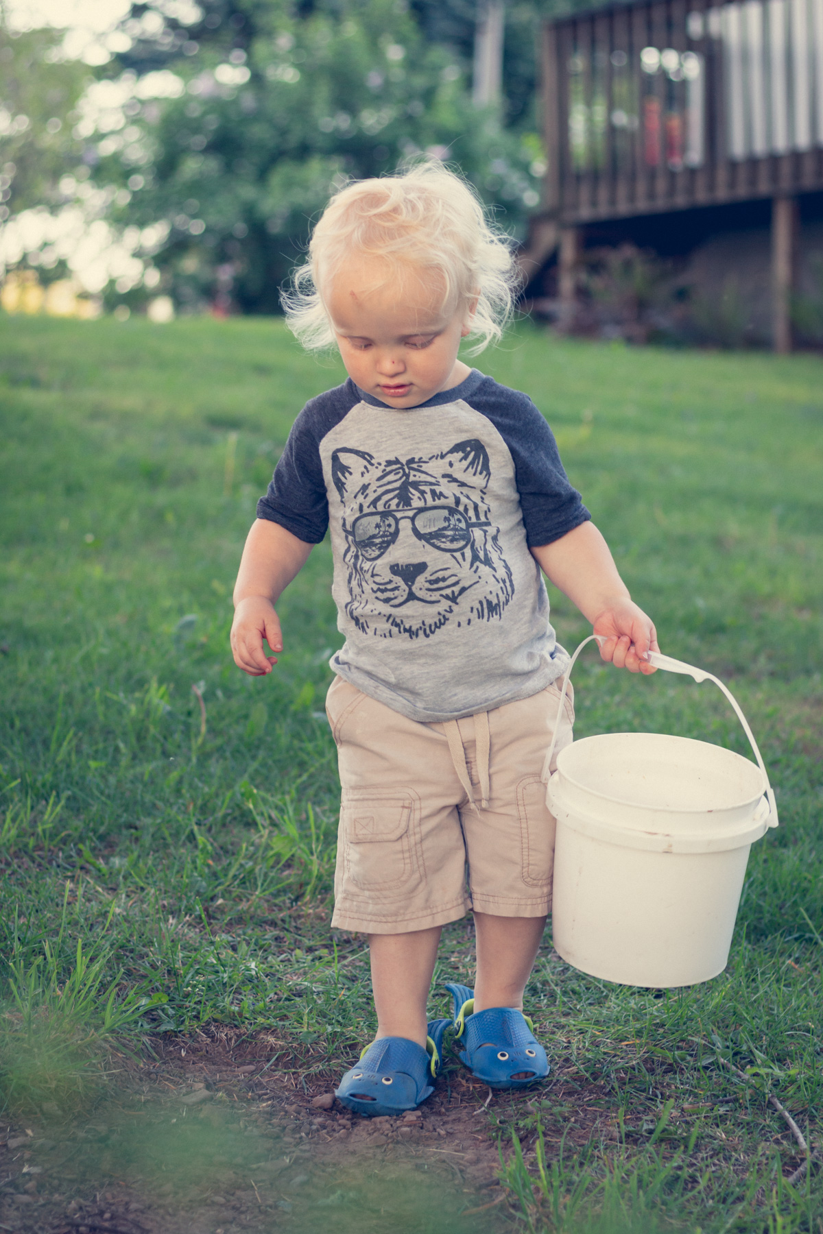 Blond boy carrying bucket outside