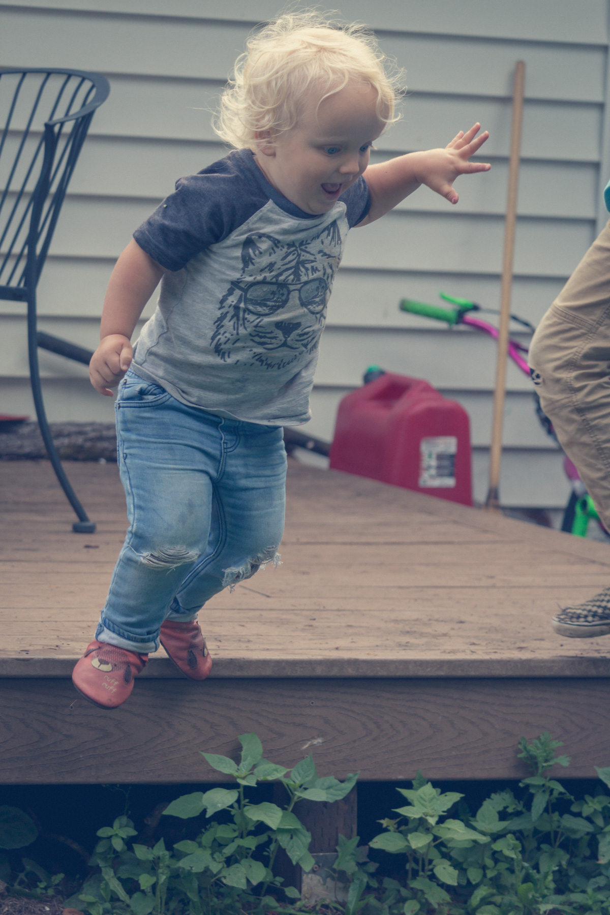 Two-year old boy jumping off house.