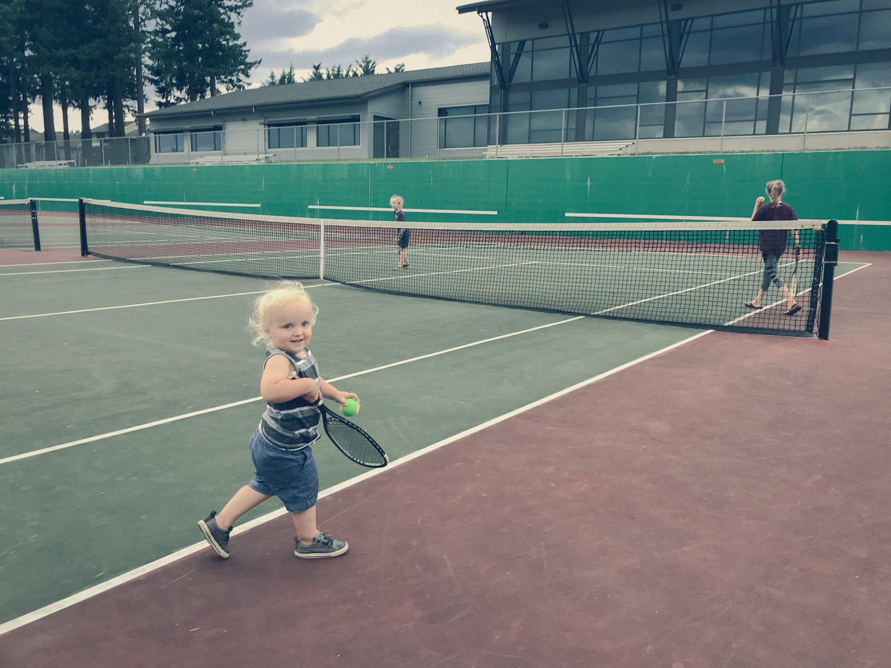 Children playing tennis and getting annihilated by their father, who is off-camera taking the photo.