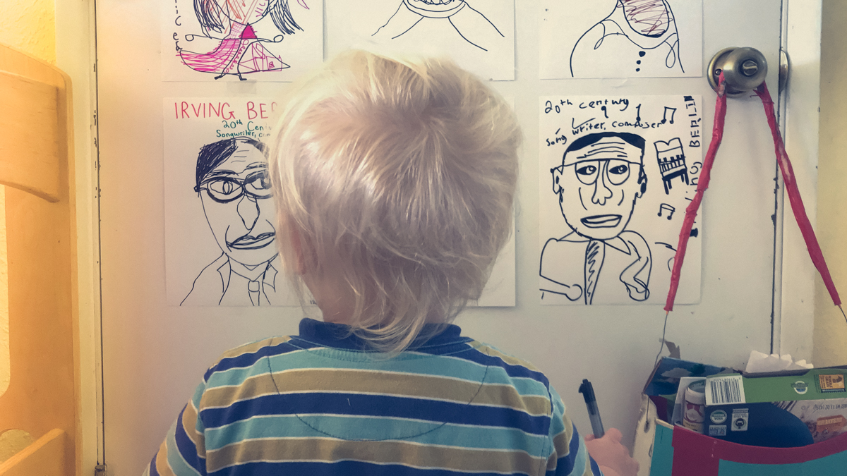 Blond boy standing in front of door with illustrations of classical composers.