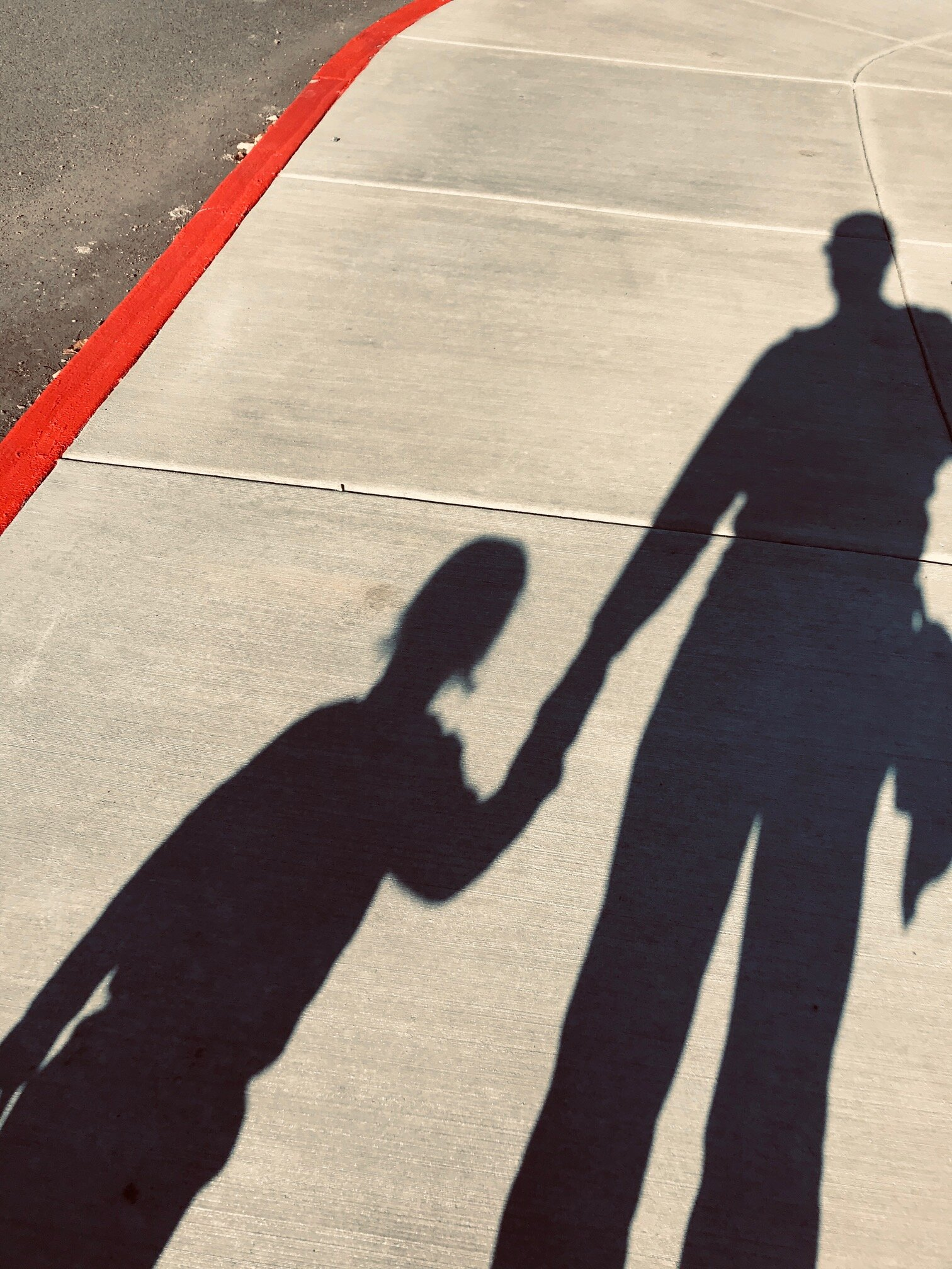 Shadow on sidewalk of dad holding young son's hand.