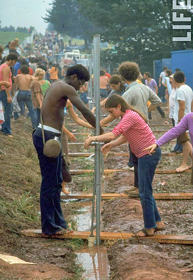Festival-goers-standing-at-water-pump-trying-to-get-water-during-a-day-at-Woodstock-1969.jpg
