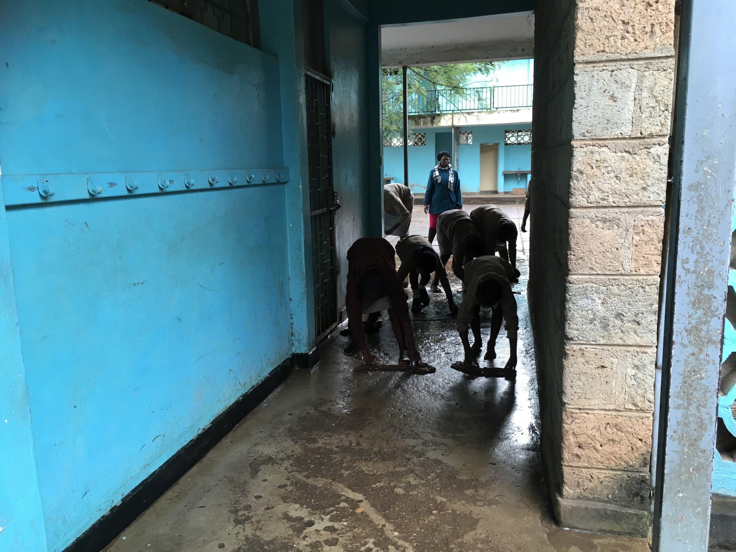 雨が降ると廊下が泥水にまみれるため、掃除する生徒たち。