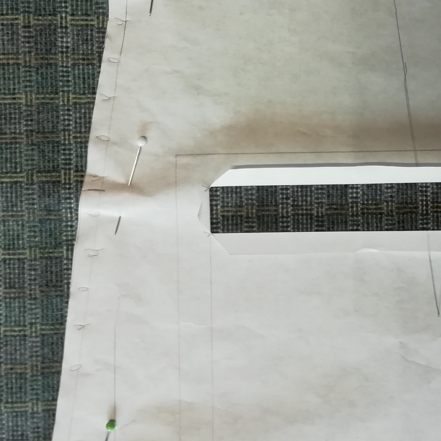 Positioning paper pattern on check fabric.