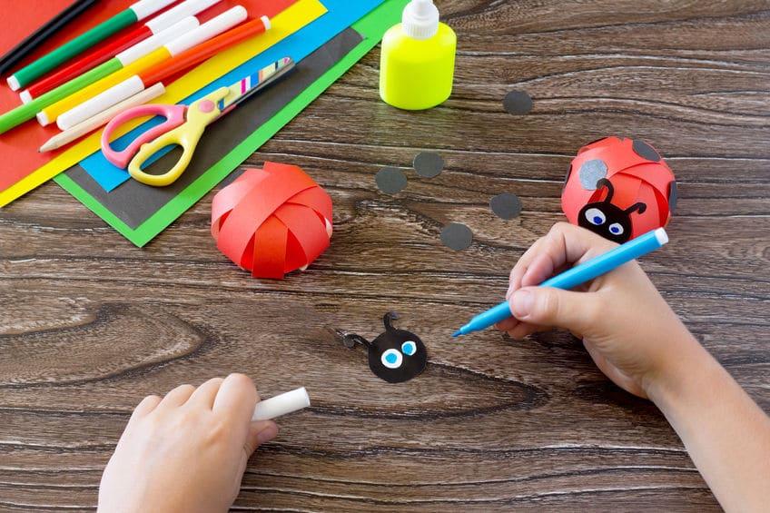3. Prenez ensuite la tête de votre coccinelle en papier, collez les deux petits ronds blancs pour faire les yeux. - Et dessinez deux petits ronds avec un feutre bleu (ou une autre couleur) au centre de ces deux ronds blancs.