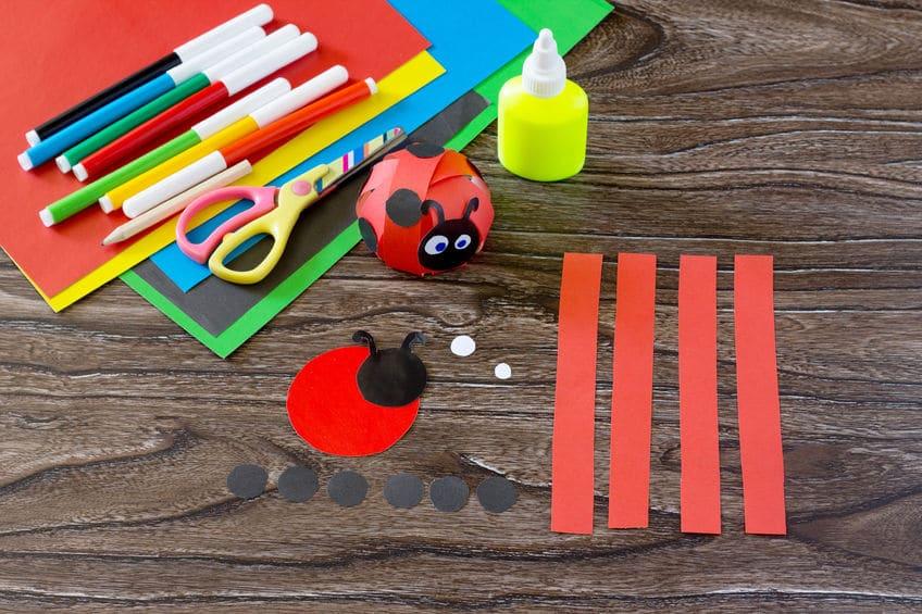 Comment réaliser cette coccinelle en papier - Utilisez le patron pour reproduire les différents éléments de la coccinelle en papier : un gros rond rouge pour la base, 4 bandes rouges pour le corps, une tête noire, deux yeux blancs, six points noirs.