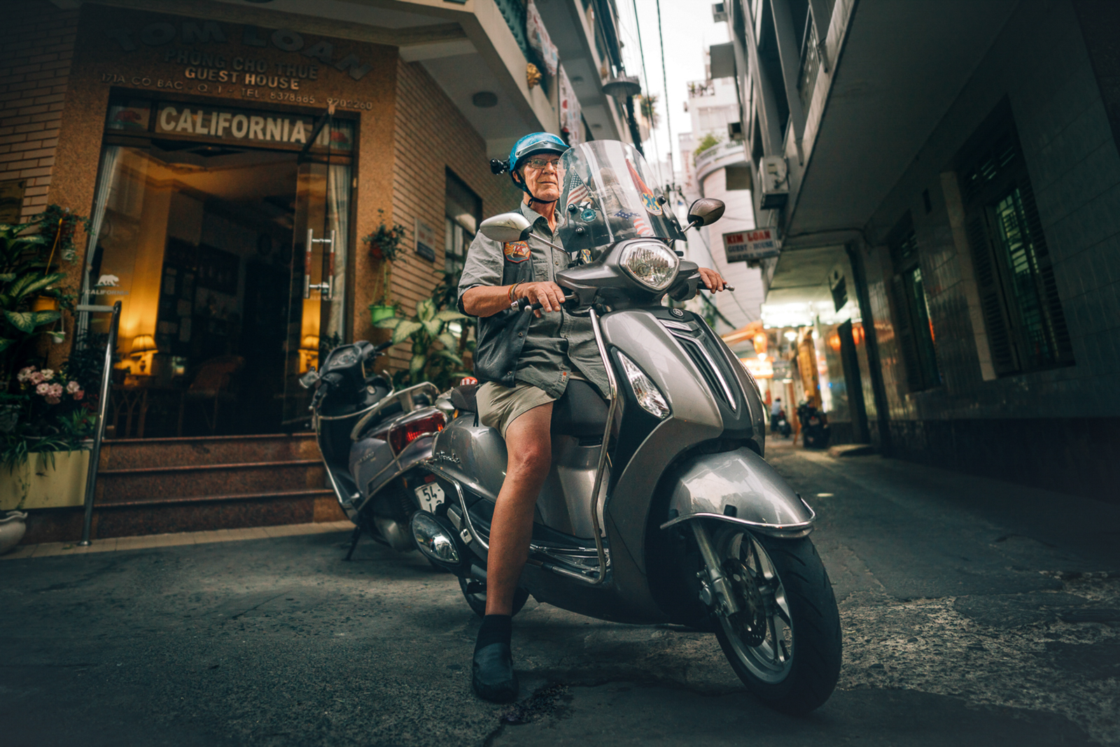 "When Bill does not live with his Vietnamese family in Cam Ranh or at Hotel California in Ho Chi Minh City, he travels on his scooter to the places where Americans were stationed as young men during the war. For years, he has been riding his motorbike through Vietnam, filming places from the past for his Veteran mates back at home in the United States with a camera installed in his helmet. ""Vietnam: Through the eyes of my brothers and sisters"" is the name of the Facebook group with more than 600 members to which he uploads the endless stream of photos and videos of today's Vietnam. The restlessness keeps Bill in the present."