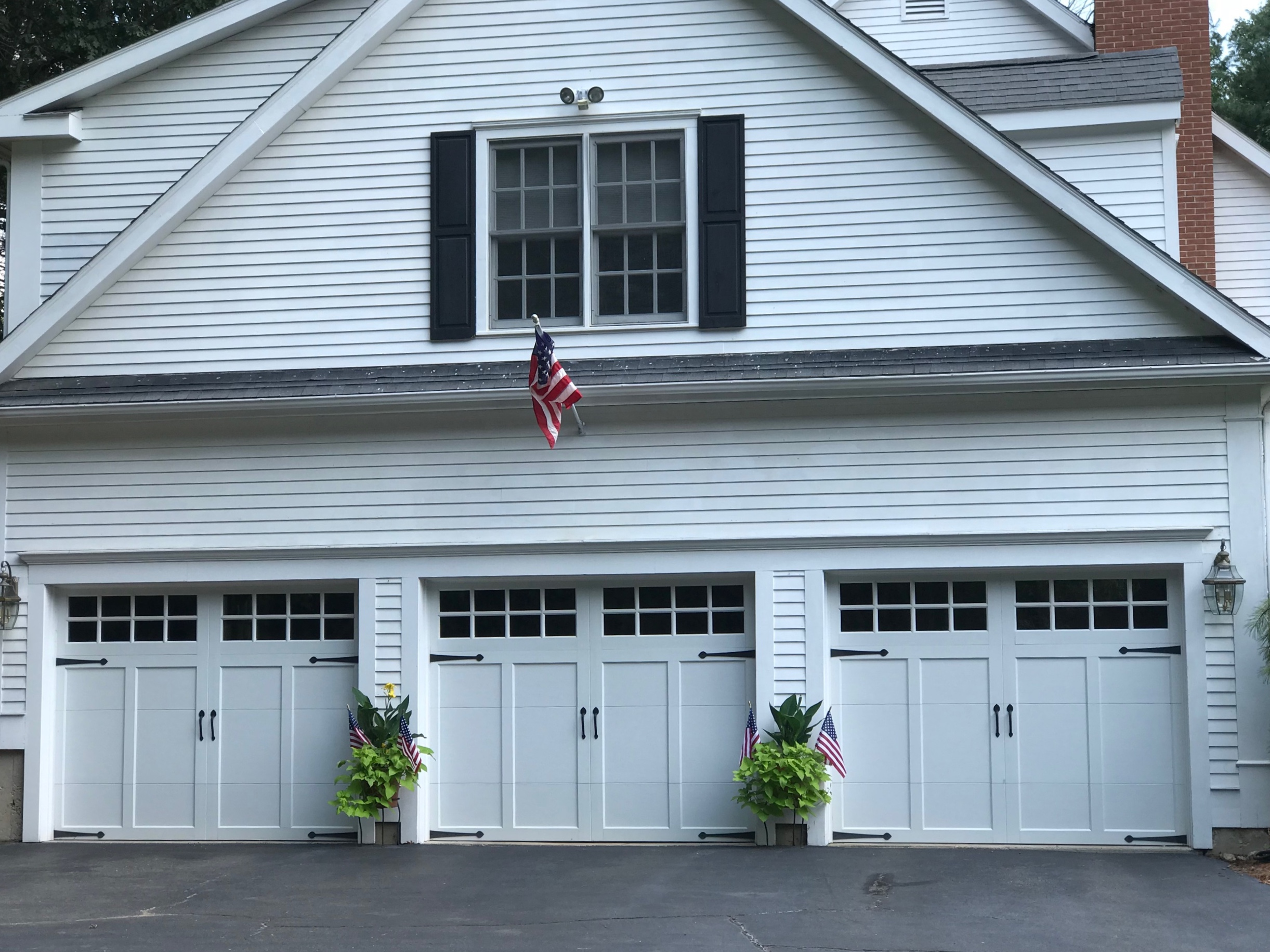 White Three Door Carriage House Style Garage with decorative hardware and windows