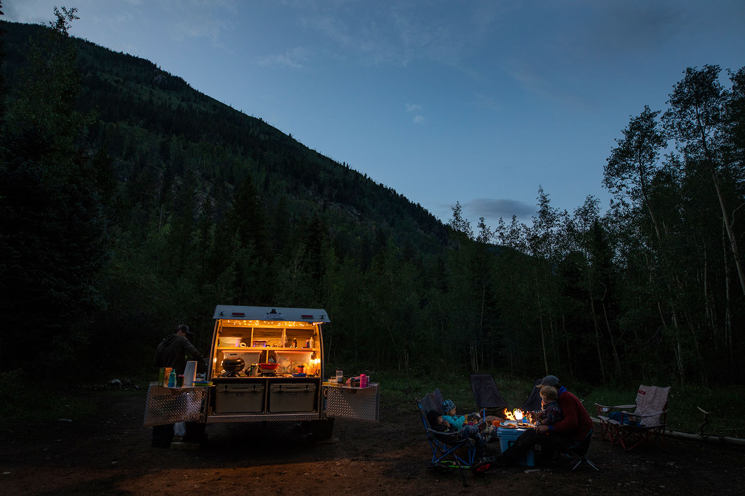 Family camping with teardrop trailer at night in the mountains