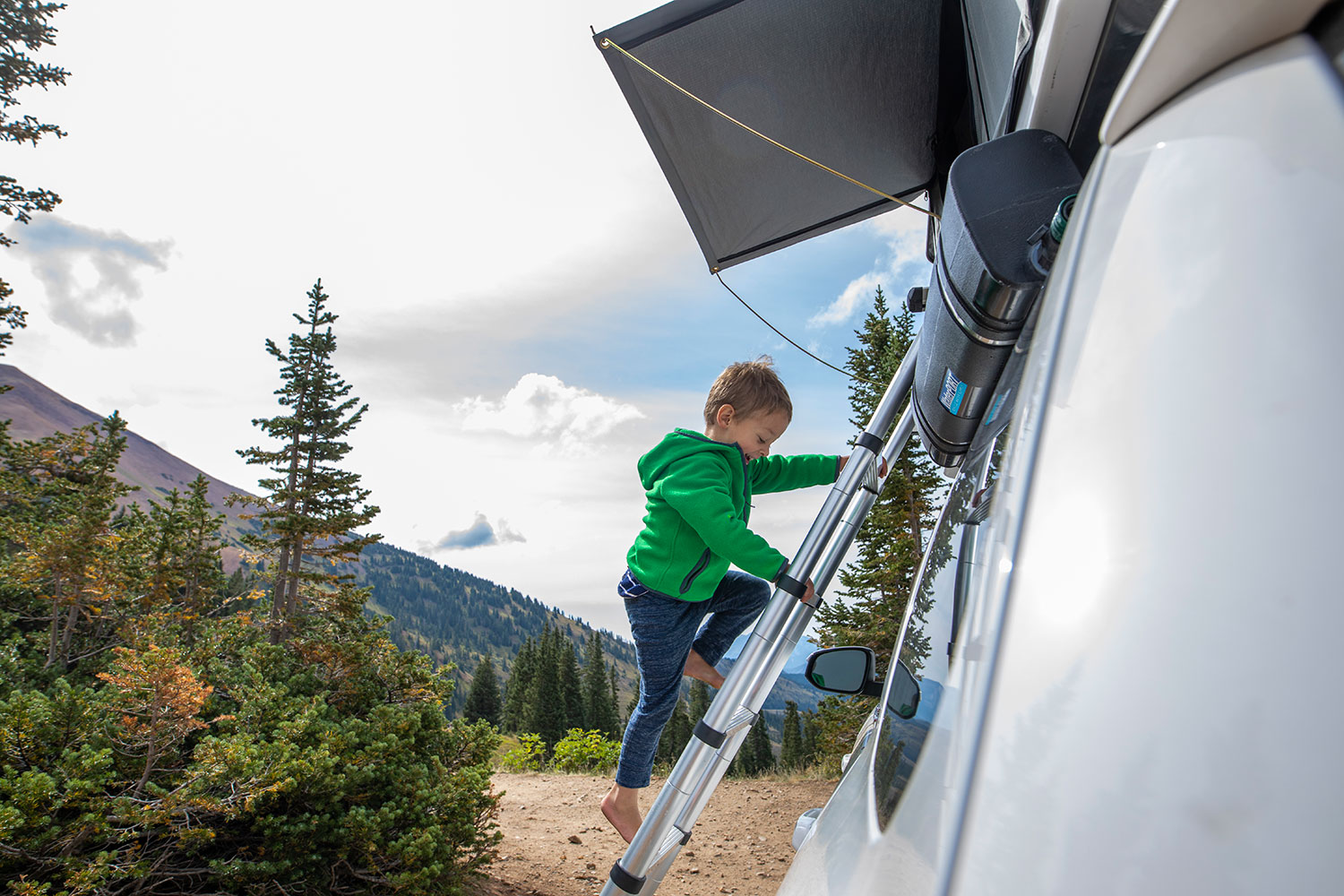 Boy climbing ladder to rooftop tent