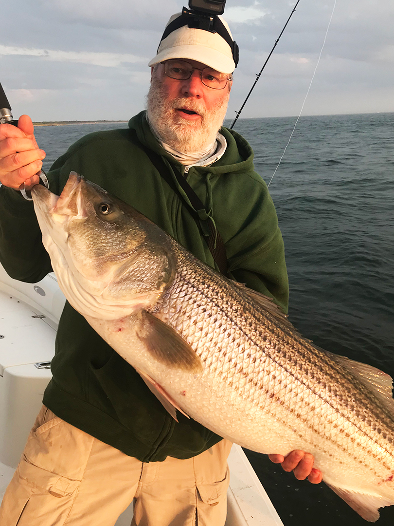 angler-john-skinner-on-charter-boat-with-striped-bass.jpg