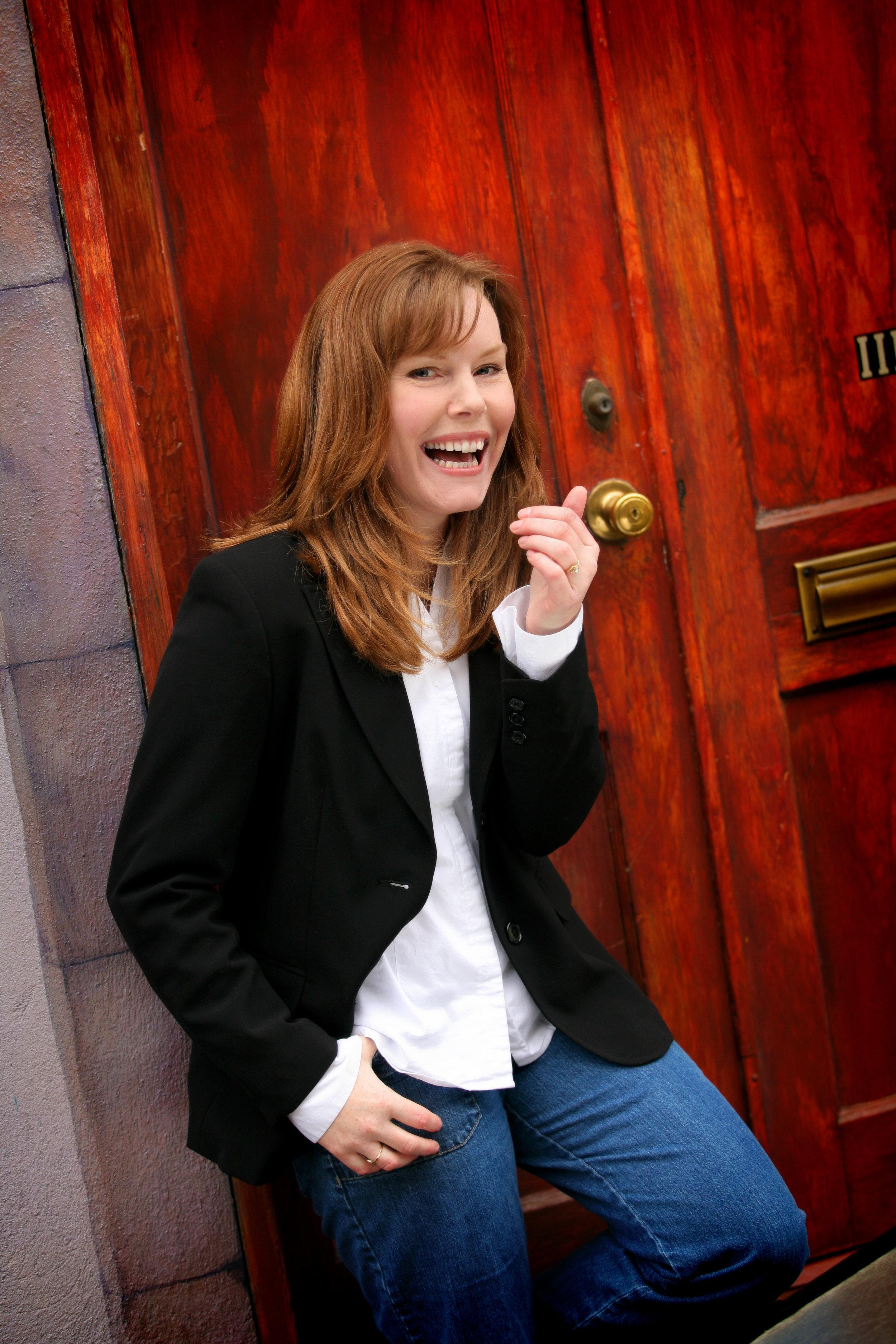 Mercedes Rose smiling in red doorway