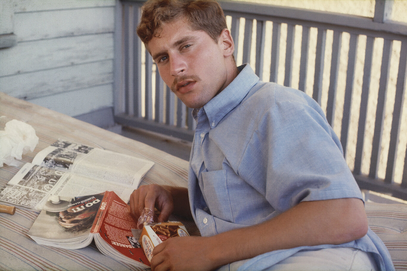 """Pfc. Robert S. Raphael, on leave, reading """"Do it!"""" on my Collegetown apartment balcony (1970)"""