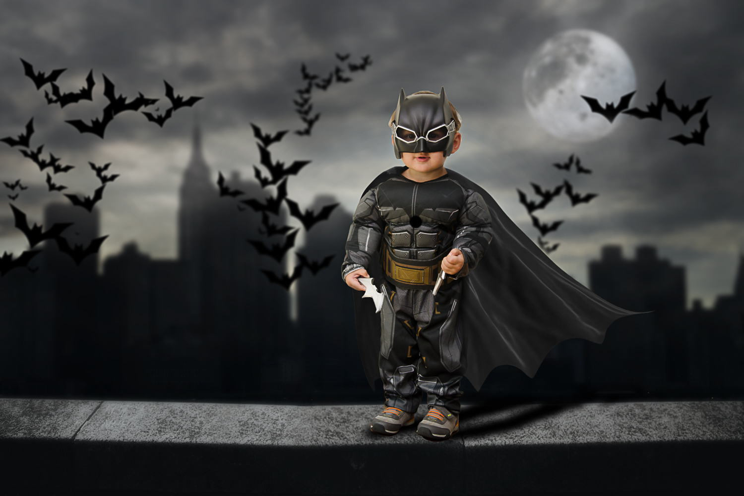 little boy batman over city skyline storybook composite