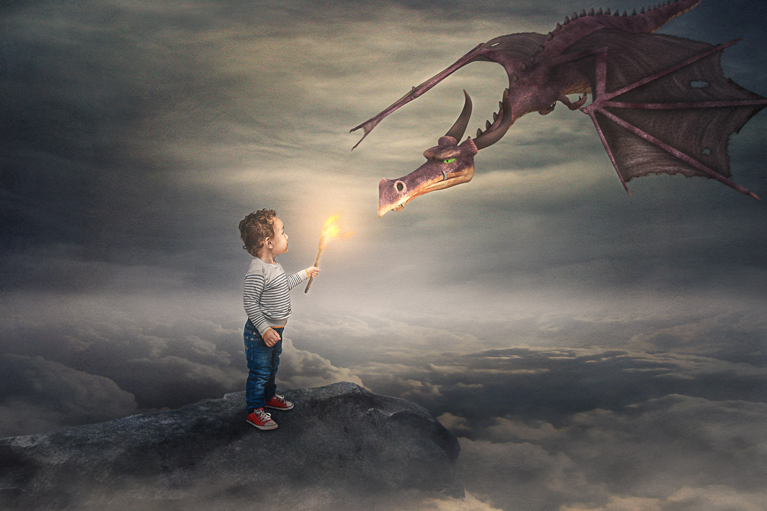 Little boy holding a torch and looking at a dragon storybook composite