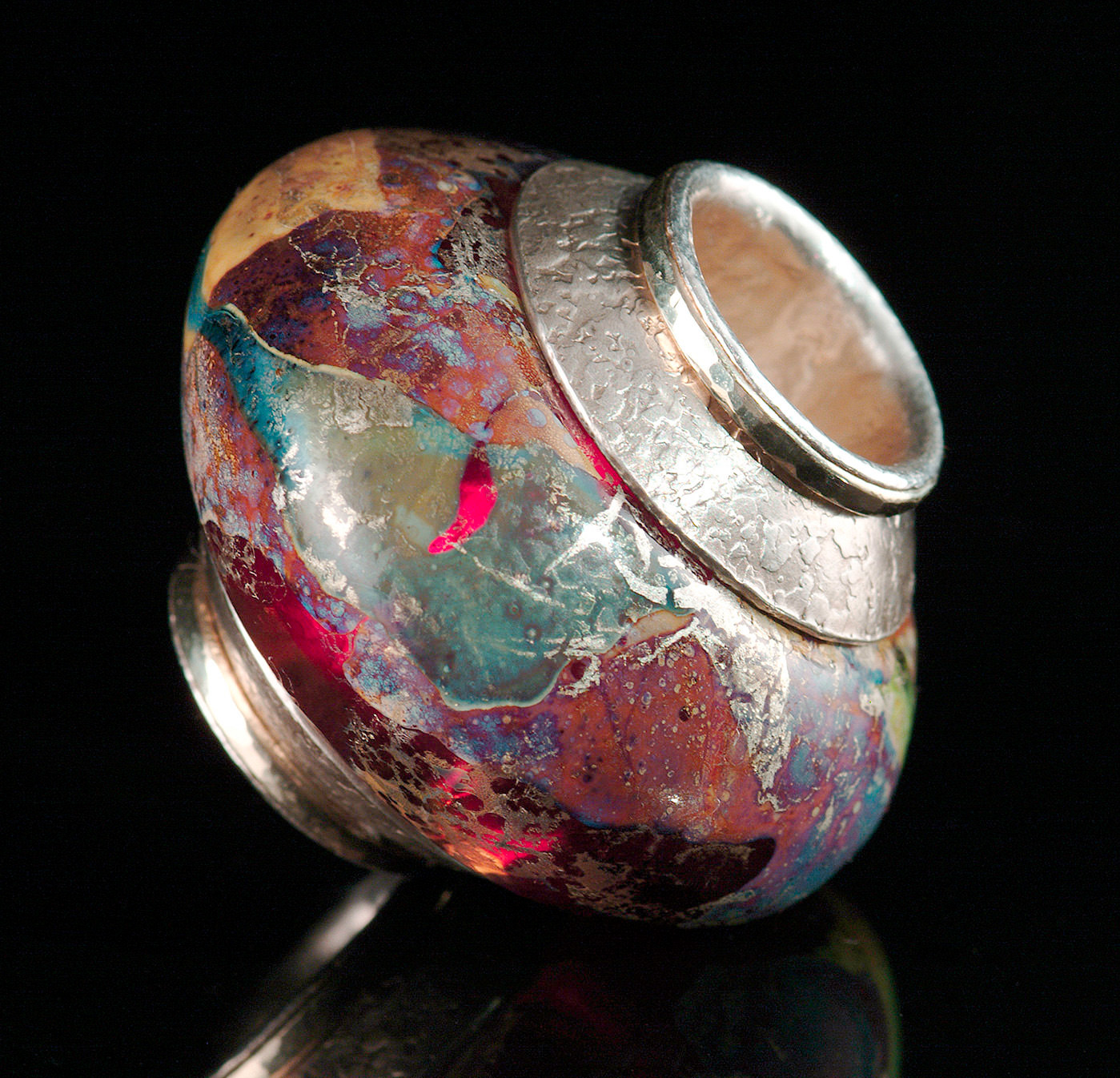 """""""Ruby Donut Bead"""", 2001, with fine silver and 14K gold. Beads in this series had very large holes and were given a high polish on the inside using diamond tools. A polished silver tube was set as a huge """"rivet"""", causing light to reflect through the transparent glass, illuminating the color from the inside. Bead is about 3.5 cm diameter."""