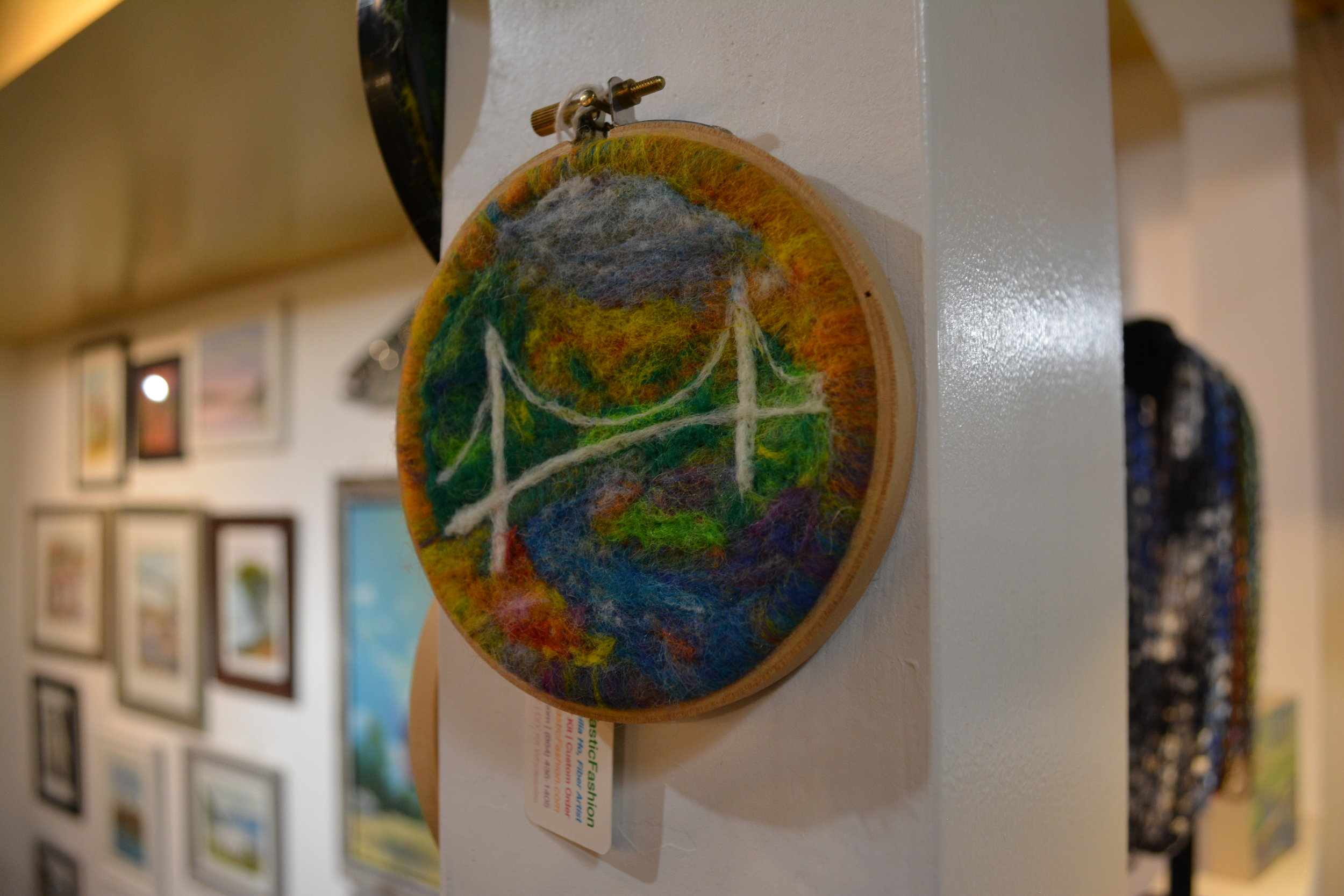 Cecilia Ho - Fiber artist using felt. Framed in circle and in framed boxes. work the captures scenes around Greenville, animals, mountains, and oceans, and flowers.