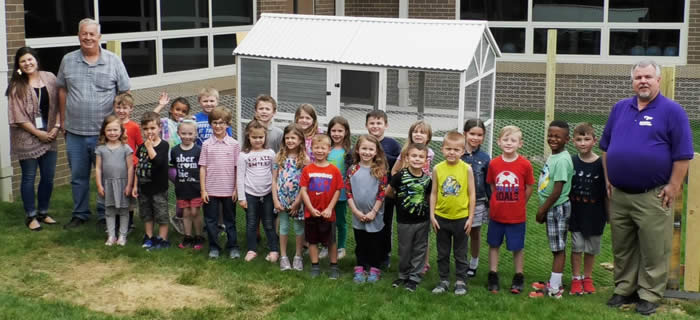 The kindergarten class responsible for the chicken coop behind Boonesborough Elementary School stands in front of the new structure along with, far left: teacher Tori Golden and head custodian Elmer Perkins, who helped build the coop, and, far right, Madison County Schools Food Services Director Scott Anderson. (Kentucky Department of Agriculture photo)